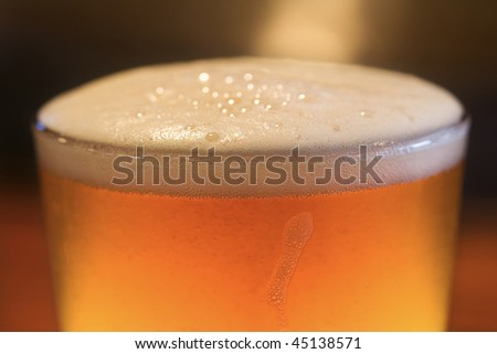 Close-up of glass of beer with foam on top. Vertical shot. - stock photo
