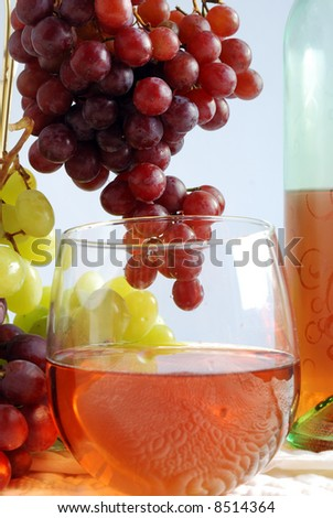 close-up of glass of white zinfandel with grapes and bottle partially in frame - stock photo