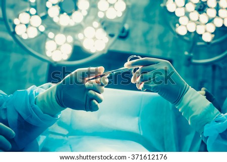 Close-up of gloved hands holding surgical scissors - stock photo
