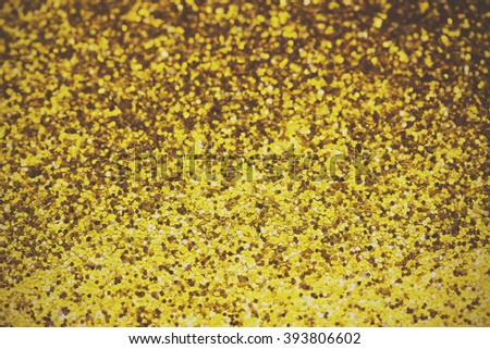 Close up of gold glitter shining in the light. Shallow depth of field. Retro filter applied.