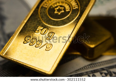 Close-up of gold-ingots on top of dollar banknotes - stock photo