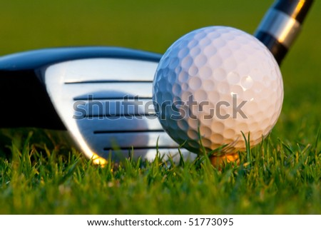 Close up of golf ball and driver head