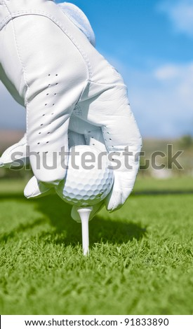 Close up of golfer's gloved hand setting up ball on tee.