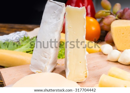 Close Up of Gourmet Cheese Board Appetizer Featuring Wedges of Brie Cheese Standing Upright on Wooden Board and Surrounded by Fresh Fruit Garnish - stock photo