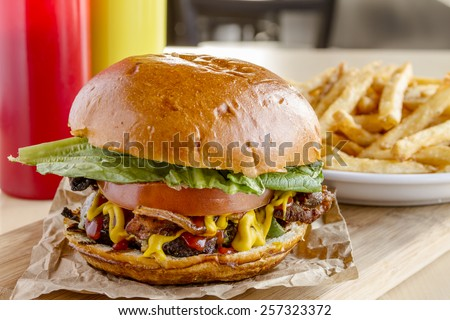 Close up of gourmet pub hamburger with bacon on wooden cutting board with plate of french fries sitting on wooden table