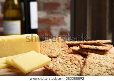 Close up of gourmet stone ground wheat crackers with white cheddar cheese - stock photo