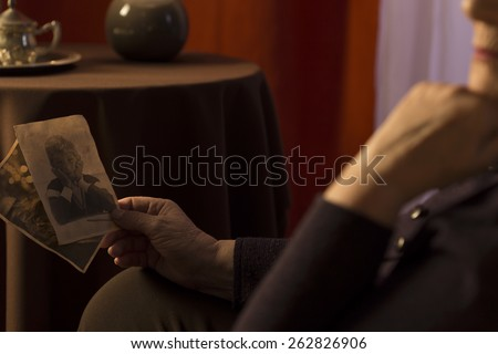 Close-up of grandmother looking at grandson picture - stock photo