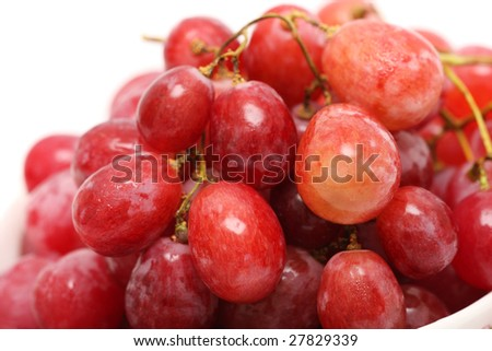 Close up of grapes in bowl over white background.