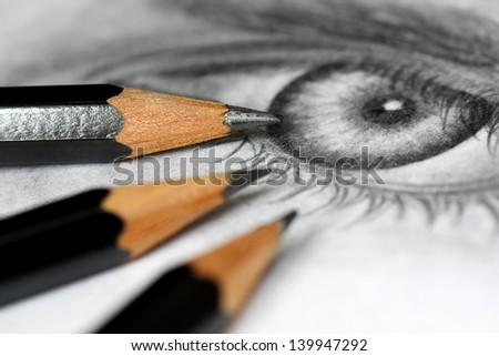 Close up of graphite drawing pencils laying on paper with eye