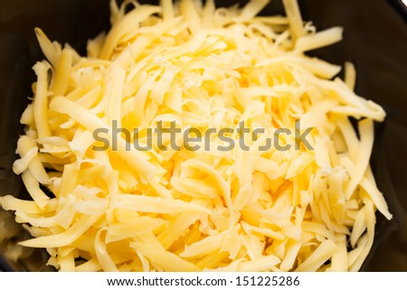 Close-up of grated cheddar cheese on a black plate. - stock photo