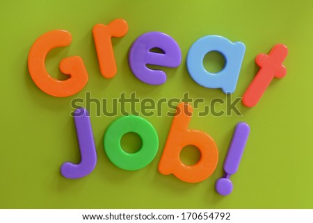 Close up of Great Job! words in colorful plastic letters on green background