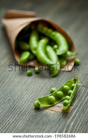 Close-up of green peas in craft paper package on dark wooden background - stock photo