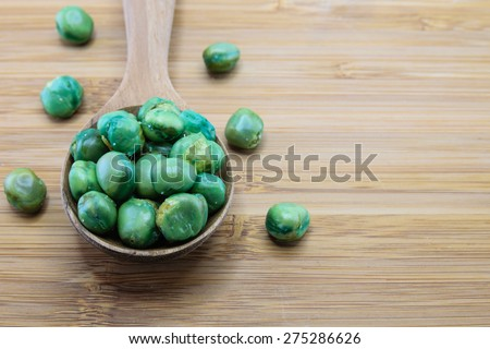Close up of green peas in spoon on wood background - stock photo