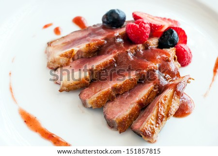 Close up of grilled duck breast covered with sweet red fruit sauce.
