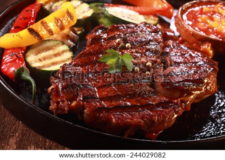 Close Up of Grilled Steak on Cast Iron Pan with Grilled Vegetables on the Side - stock photo