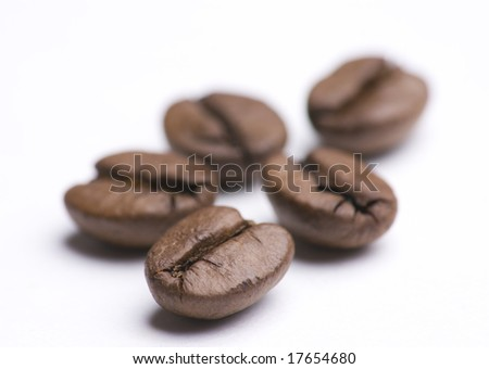 Close up of group of coffee beans isolated on white background