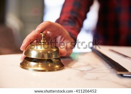 Close Up Of Guest's Hand On Hotel Reception Bell