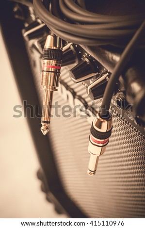 Close-up of guitar amplifier with jack cable. - stock photo