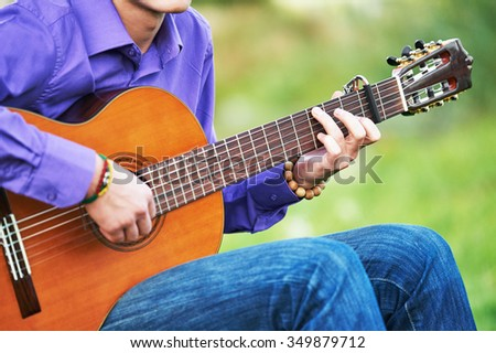 Close up of guitarist hands playing music chords on acoustic six string guitar outdoors - stock photo