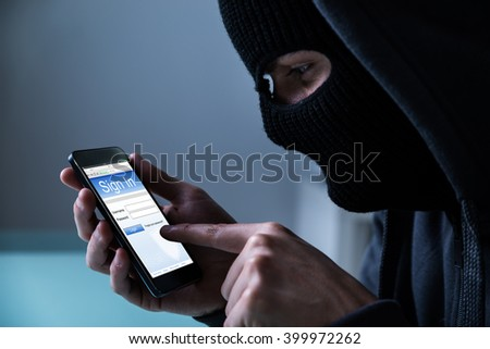 Close-up Of Hacker Using Smart Phone To Steal Data In Office - stock photo