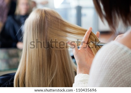 Close up of hairdresser giving a new haircut to female customer at parlor - stock photo