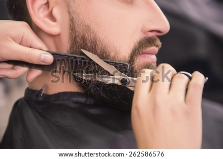 Close-up of hairdresser shaving  with scissors and combs of satisfied client in professional hairdressing salon. - stock photo