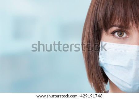 Close-up of half face and right eye of woman doctor with mask against blue background with text area - stock photo