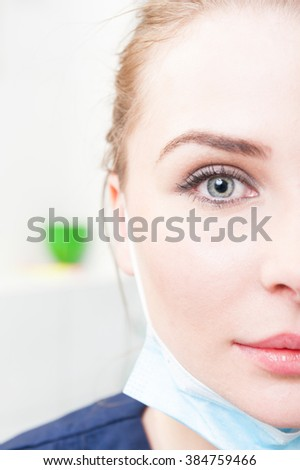 Close-up of half face of beautiful female dentist with perfect skin in dental office - stock photo