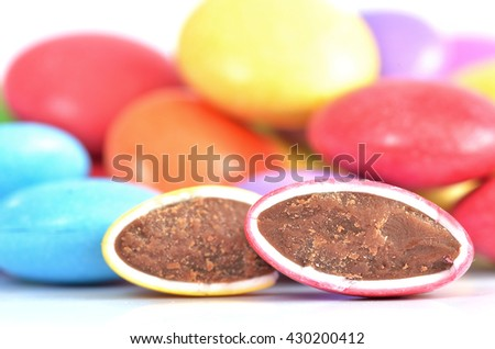 Close-up of halved red and yellow candies with chocolate filling and blue, purple, yellow candies in background - stock photo