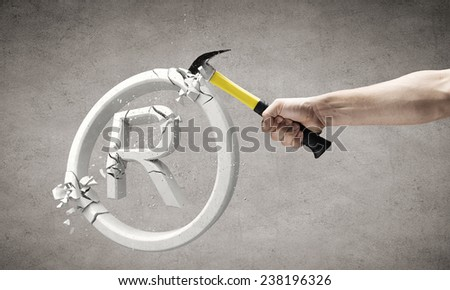 Close up of hammer in human hand breaking trade mark - stock photo