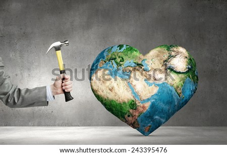 Close up of hammer in human hand hitting Earth planet. Elements of this image are furnished by NASA - stock photo
