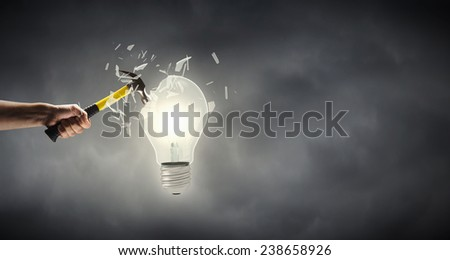 Close up of hammer in human hand hitting light bulb