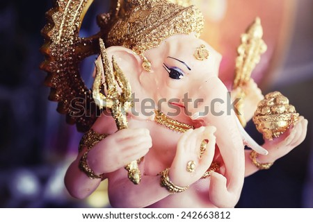 Close-up of hand crafted clay idol of Hindu god Ganesha - Lord of good omen in dramatic light - stock photo