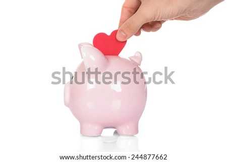Close-up Of Hand Deposit Red Heart In Piggy Bank Over White Background - stock photo