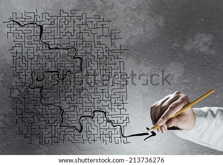 Close up of hand drawing labyrinth on cement wall - stock photo