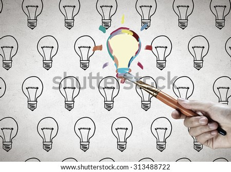 Close up of hand drawing light bulb with marker - stock photo