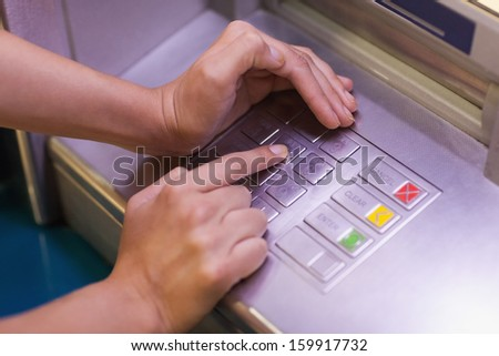 Close up of hand entering pin at an ATM - stock photo