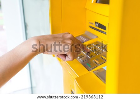 Close-up of hand entering PIN on ATM - stock photo