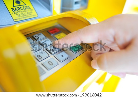 Close up of hand entering PIN/pass code on ATM/bank machine keypad - stock photo