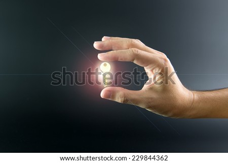 Close up of hand holding a key over black background - stock photo