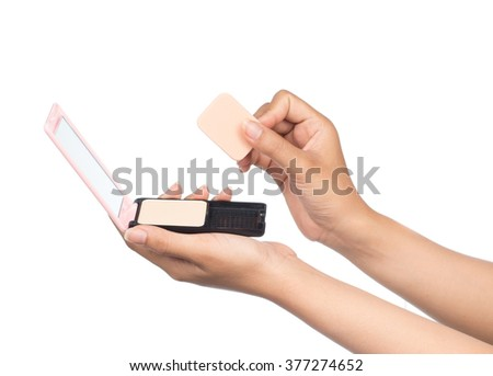 Close up of hand holding cosmetic sponges with powder isolated on a white background