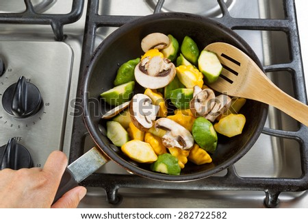 Close up of hand holding frying pan, focus on food, while stirring vegetables with wooden spoon. - stock photo