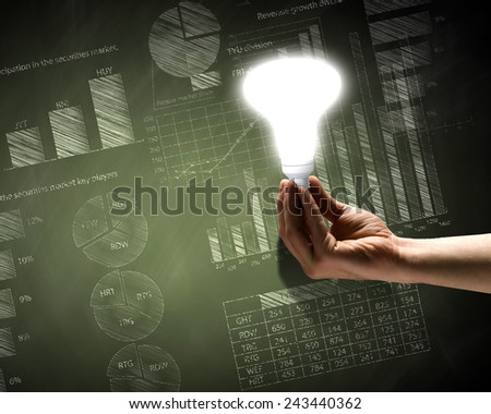 Close up of hand holding light bulb with sketches at background - stock photo