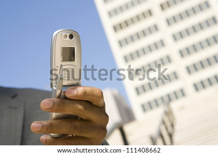 Close up of hand holding mobile phone with building in the background