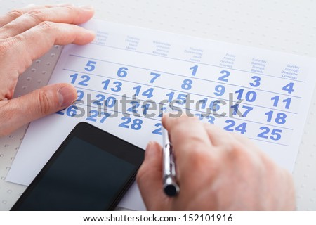 Close-up Of Hand Holding Pen Over Calendar With Mobile Phone - stock photo