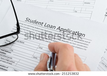 Close-up Of Hand Holding Pen Over Student Loan Application - stock photo