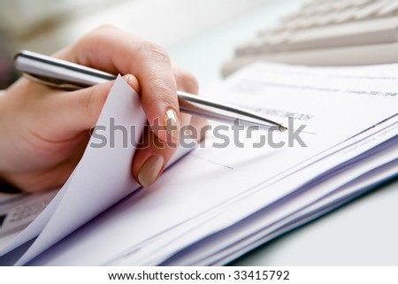 Close-up of  hand holding pen with paper over pile of documents - stock photo