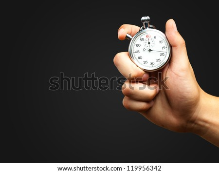 Close Up Of Hand Holding Stopwatch against a black background - stock photo