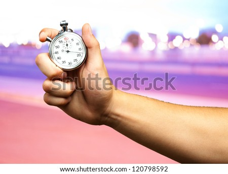 Close Up Of Hand Holding Stopwatch at a city by night - stock photo
