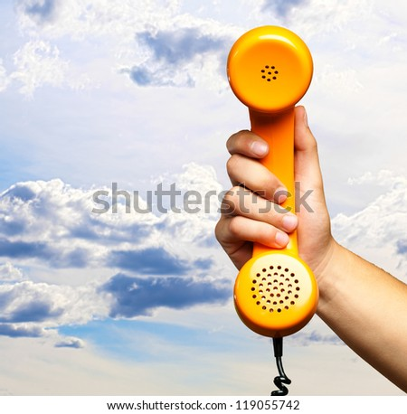 Close Up Of Hand Holding Telephone against a cloudy sky background